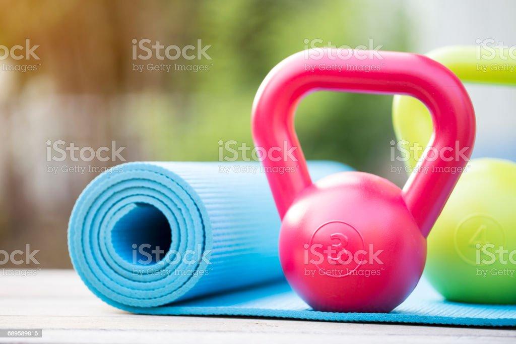 Kettlebell und Yoga-Matte auf Holztisch – Foto