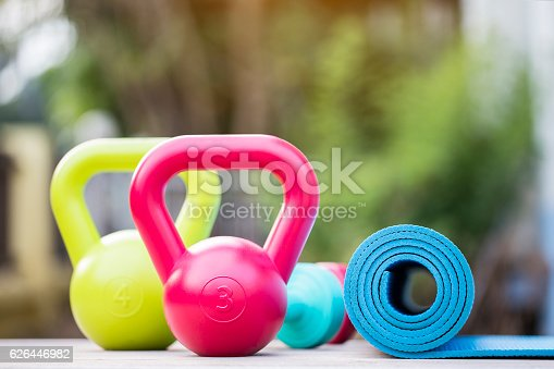 Kettlebell, dumbbell and yoga mat on wood table
