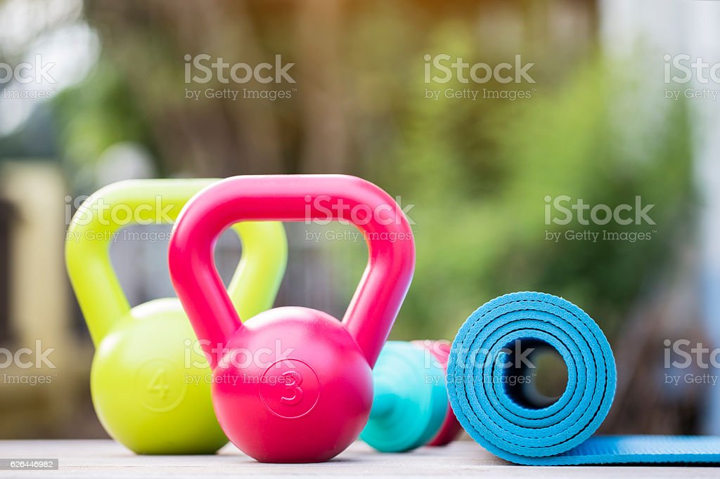 Kettlebell, dumbbell and yoga mat on wood table stock photo