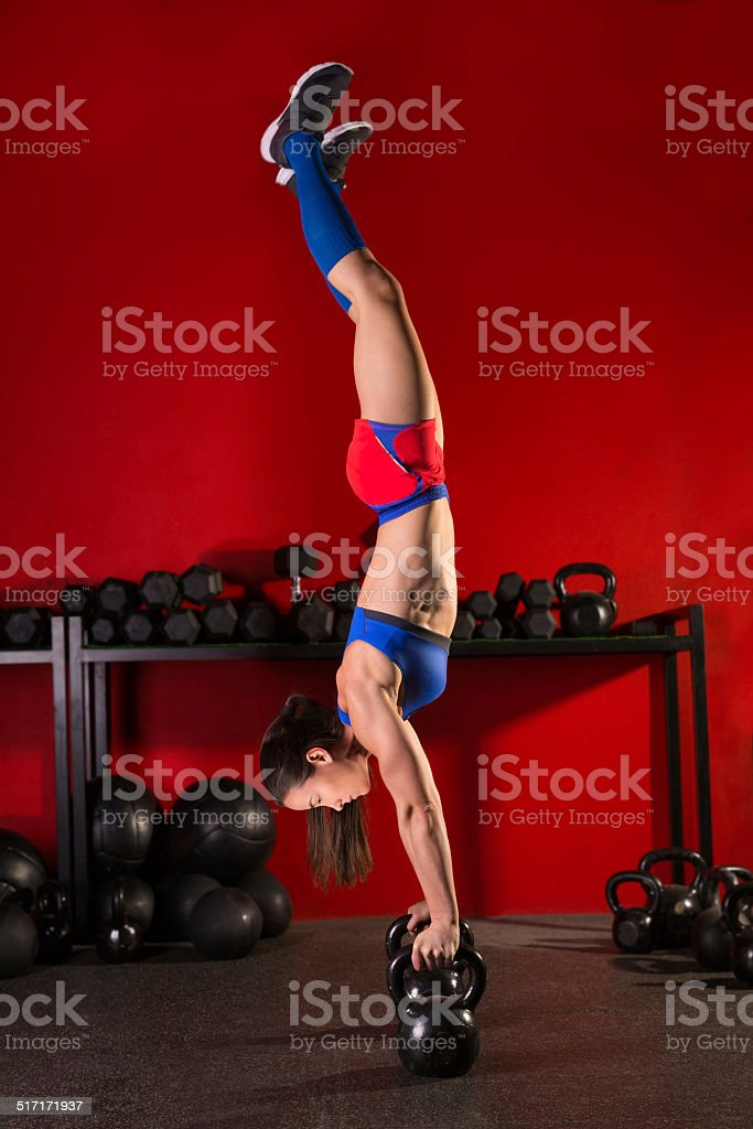 kettlebell handstand woman workout in red gym stock photo