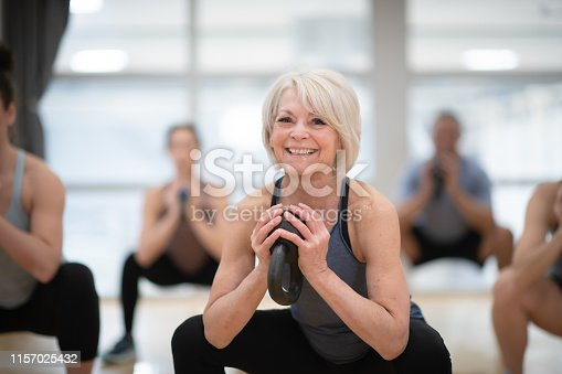 A group of diverse and athletic friends take a kettlebell class together one afternoon. They are working on their endurance as they hold the squat position.