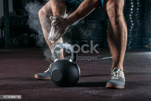 944655208 istock photo Kettlebell training in gym. Athlete doing workout 1075069730