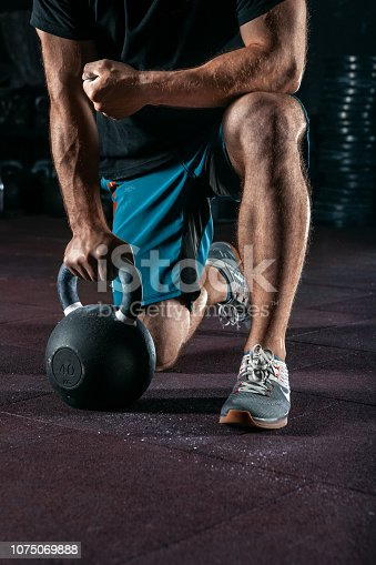 944655208 istock photo Kettlebell training in gym. Athlete doing workout 1075069888