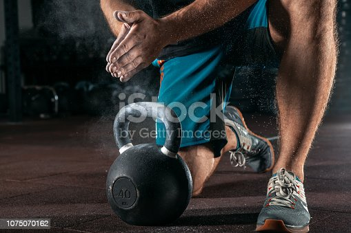 944655208 istock photo Kettlebell training in gym. Athlete doing workout 1075070162