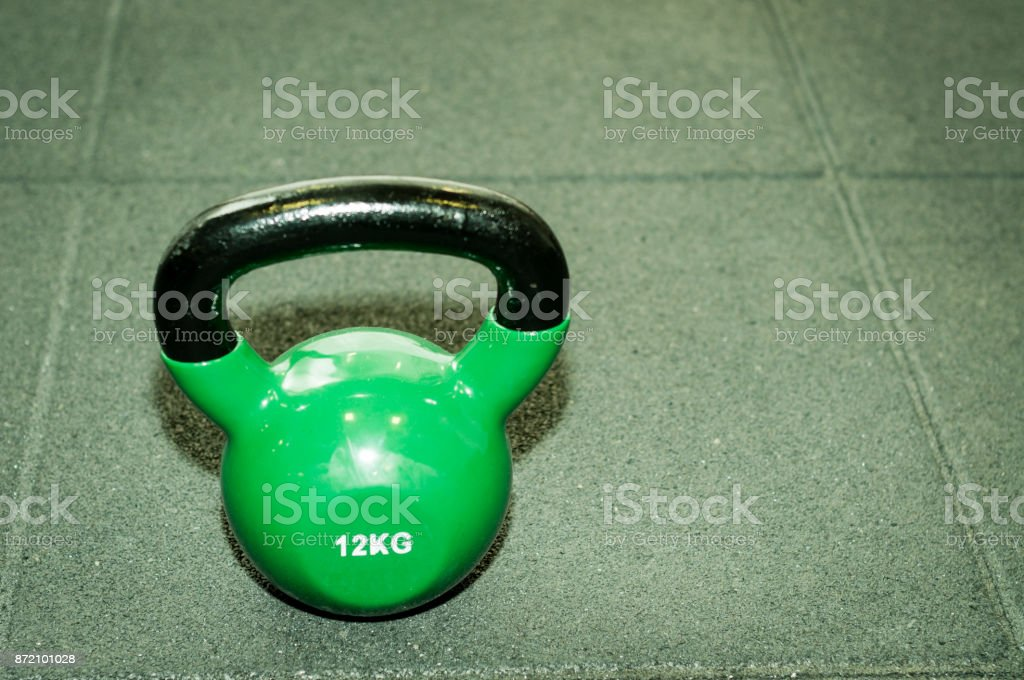 Kettlebell weight on the black gym floor with selective focus and film grain stock photo