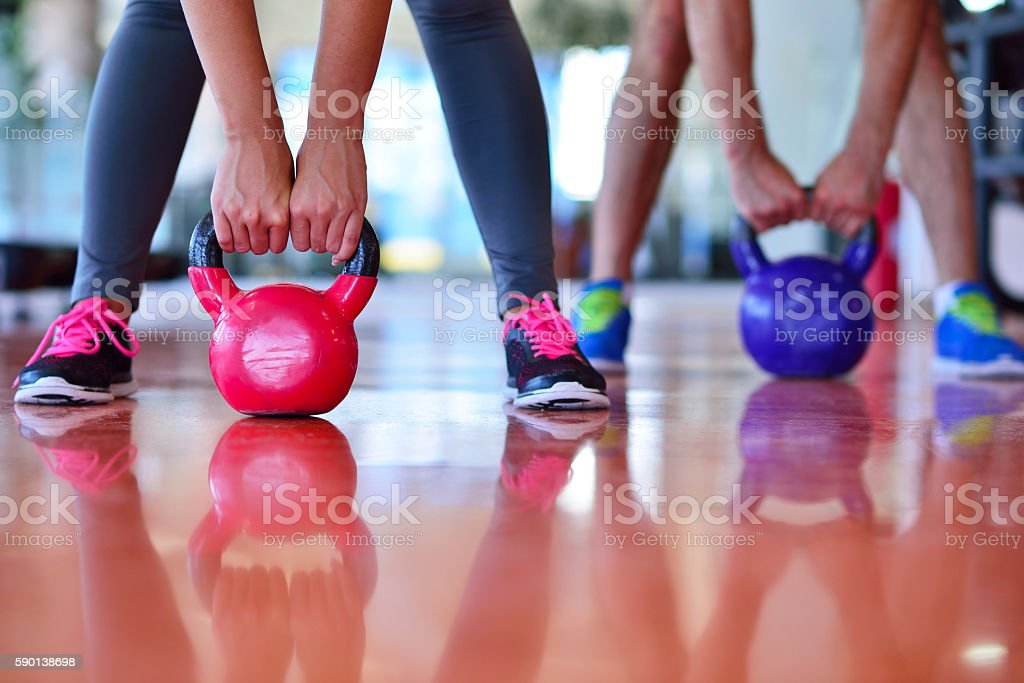 Kettlebells swing exercise man and woman workout at gym stock photo
