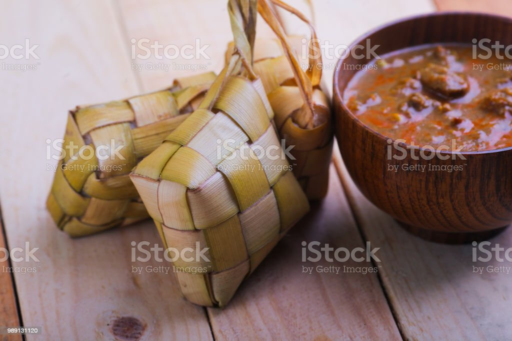 Ketupat (Rice Dumpling) and curry On wooden Background. Ketupat is a natural rice casing made from young coconut leaves for cooking rice during eid Mubarak. stock photo