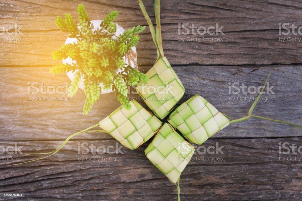 Ketupat (Reis Knödel) und Reis auf Holz-Hintergrund. Ketupat ist eine Naturreis Gehäuse aus jungen Kokosnuss Blätter zum Kochen von Reis während der Eid Mubarak. – Foto