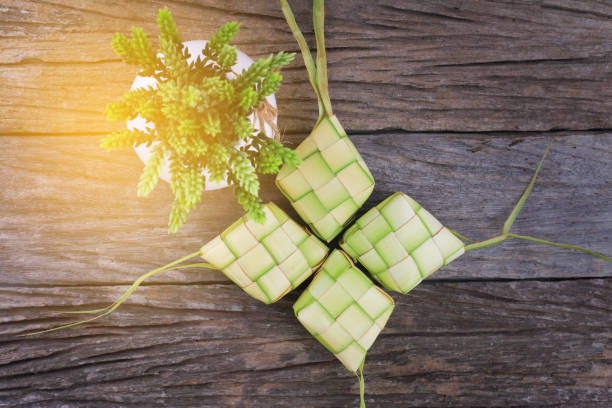 ketupat (rice dumpling) and rice on wood background. ketupat is a natural rice casing made from young coconut leaves for cooking rice during eid mubarak. - ketupat stock pictures, royalty-free photos & images