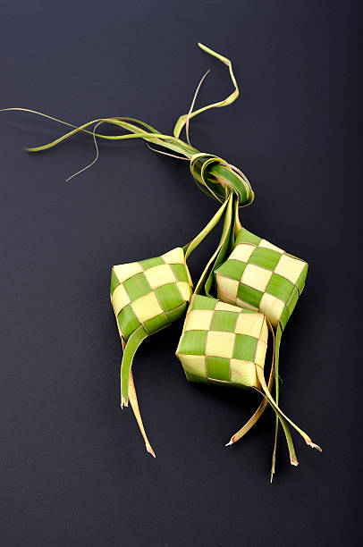 ketupat (rice dumpling) on black background - ketupat stock pictures, royalty-free photos & images