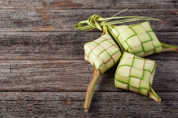 ketupat (rice dumpling) on wood background. - ketupat stock pictures, royalty-free photos & images