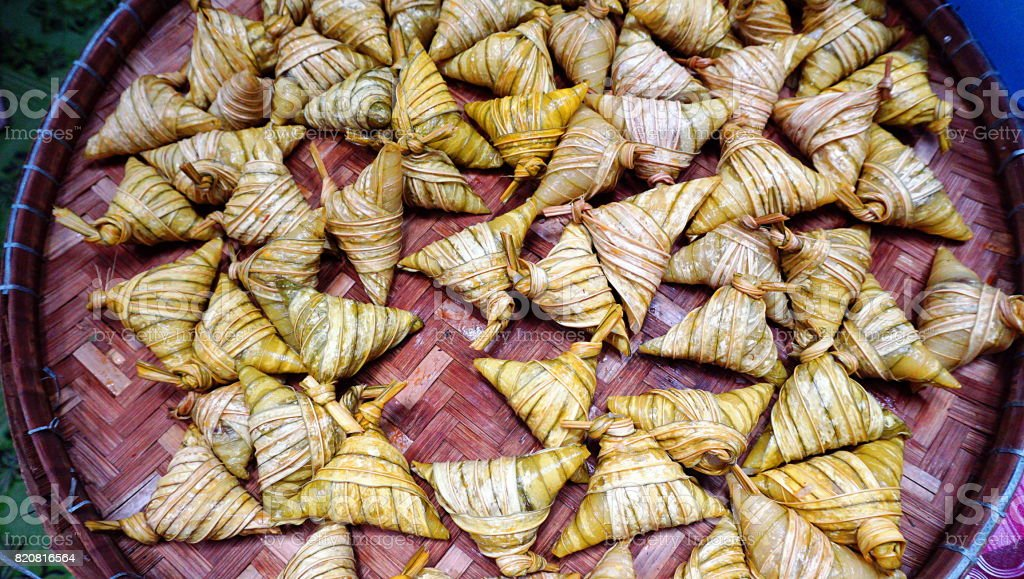 Ketupat palas, a Malay delicacy made from glutinous rice and coconut milk packed inside a diamond shaped container made of wooven palm leaf also known as daun palas. stock photo