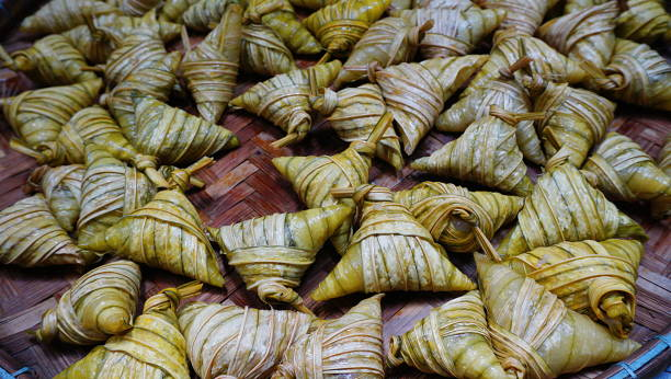 ketupat palas, a malay delicacy made from glutinous rice and coconut milk packed inside a diamond shaped container made of wooven palm leaf also known as daun palas. - ketupat stock pictures, royalty-free photos & images