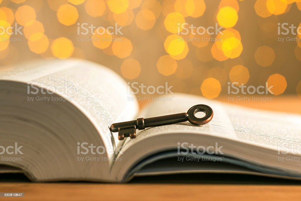 key and book with flares background stock photo