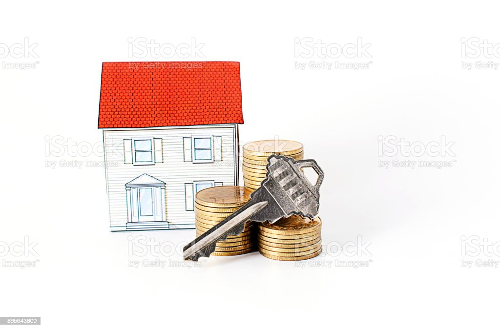 key and coins stack and paper house on white background stock photo