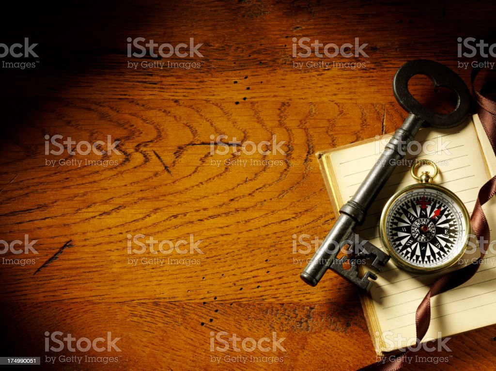 Key and Compass on a Book with Ribbon stock photo
