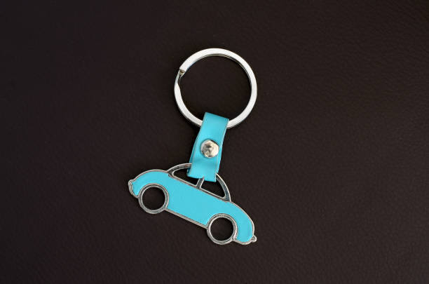 Key chain with cyan beetle car on dark leather pad as background stock photo