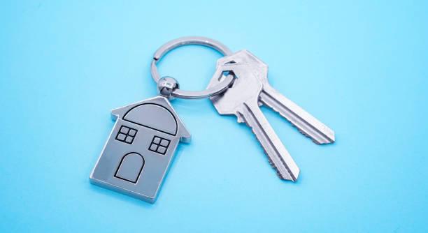 파란색 배경에 집 기호와 키가 있는 키 체인, 부동산 개념 - home 뉴스 사진 이미지