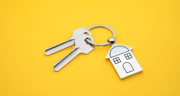 노란색 배경에 집 기호와 키가 있는 키 체인, 부동산 개념 - home 뉴스 사진 이미지