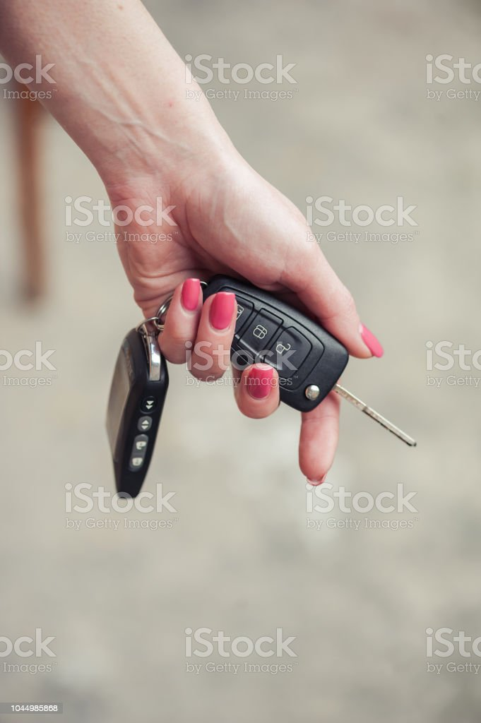 Key from the car in a female hand. Car seller. Opening and signaling
