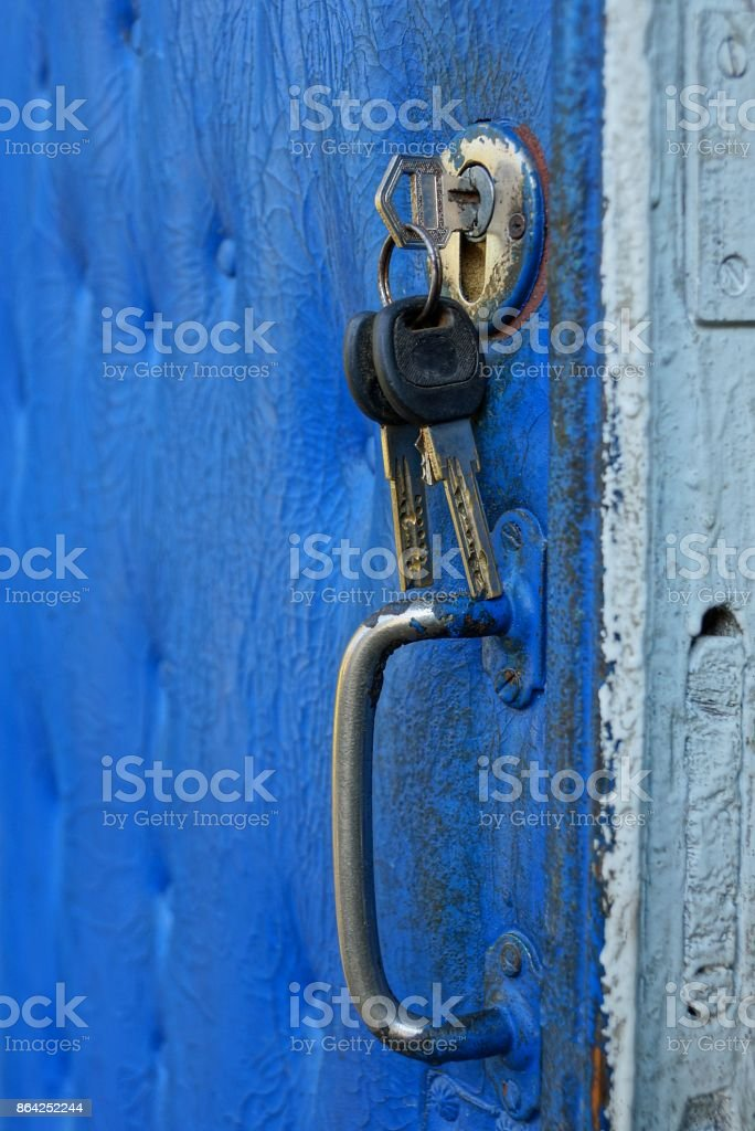 key in the keyhole on the blue old door royalty-free stock photo