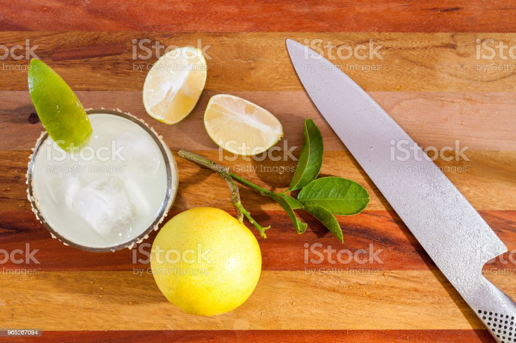 Key lime margarita garnished with fresh lime in a glass bar table chife knife. view from above zbiór zdjęć royalty-free