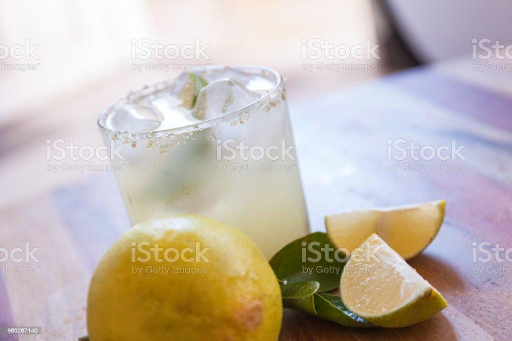 Key lime margarita garnished with fresh lime in a glass bar table zbiór zdjęć royalty-free