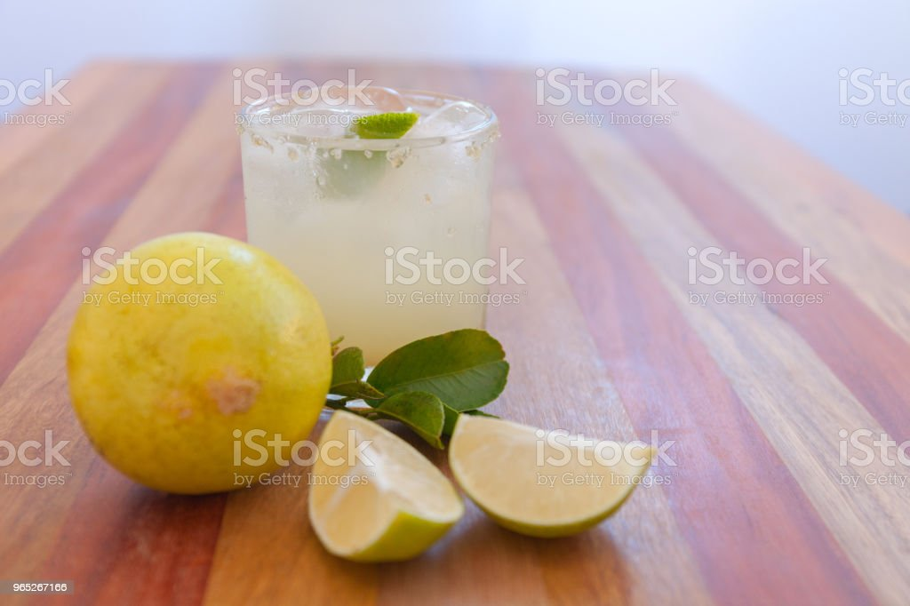 Key lime margarita garnished with fresh lime in a glass bar table royalty-free stock photo