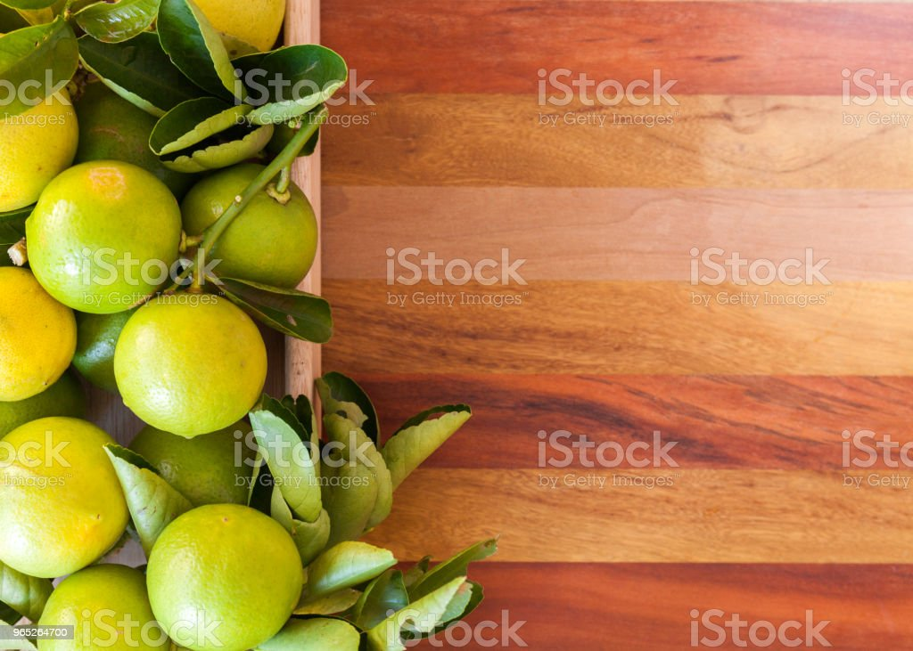Key lime or Mexican lime in a wooden box on floor, one of main ingredient thai food and traditional pie. horizontal royalty-free stock photo