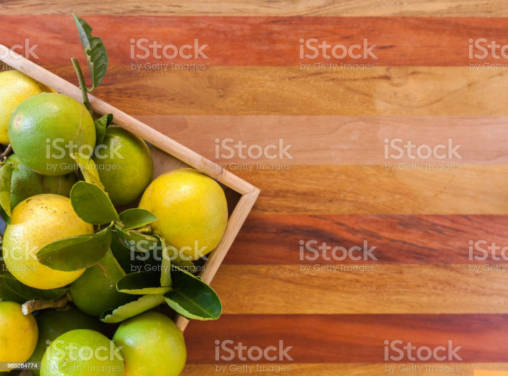 Key lime or Mexican lime in a wooden box on floor, one of main ingredient thai food and traditional pie. free space for text royalty-free stock photo
