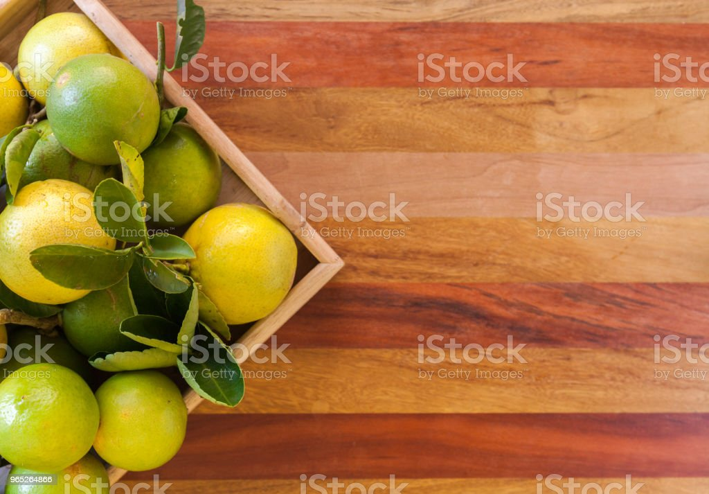 Key lime or Mexican lime in a wooden box on floor, one of main ingredient thai food and traditional pie. free space for text. horizontal royalty-free stock photo
