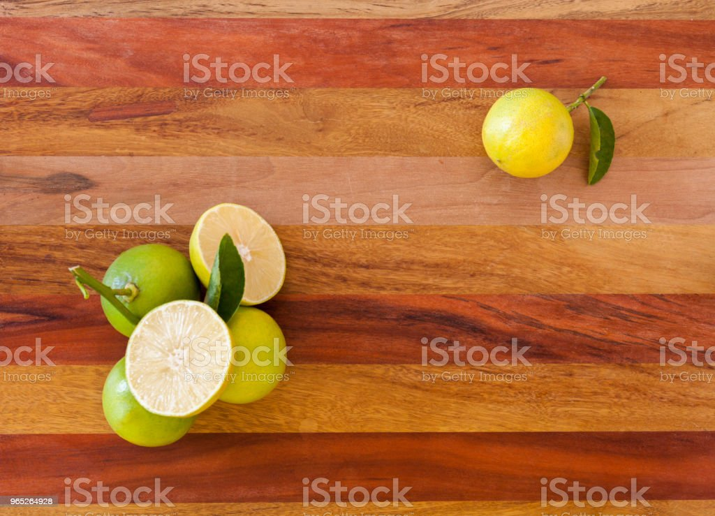 Key lime or Mexican lime on wooden table, one of main ingredient thai food and traditional pie. horizontal royalty-free stock photo