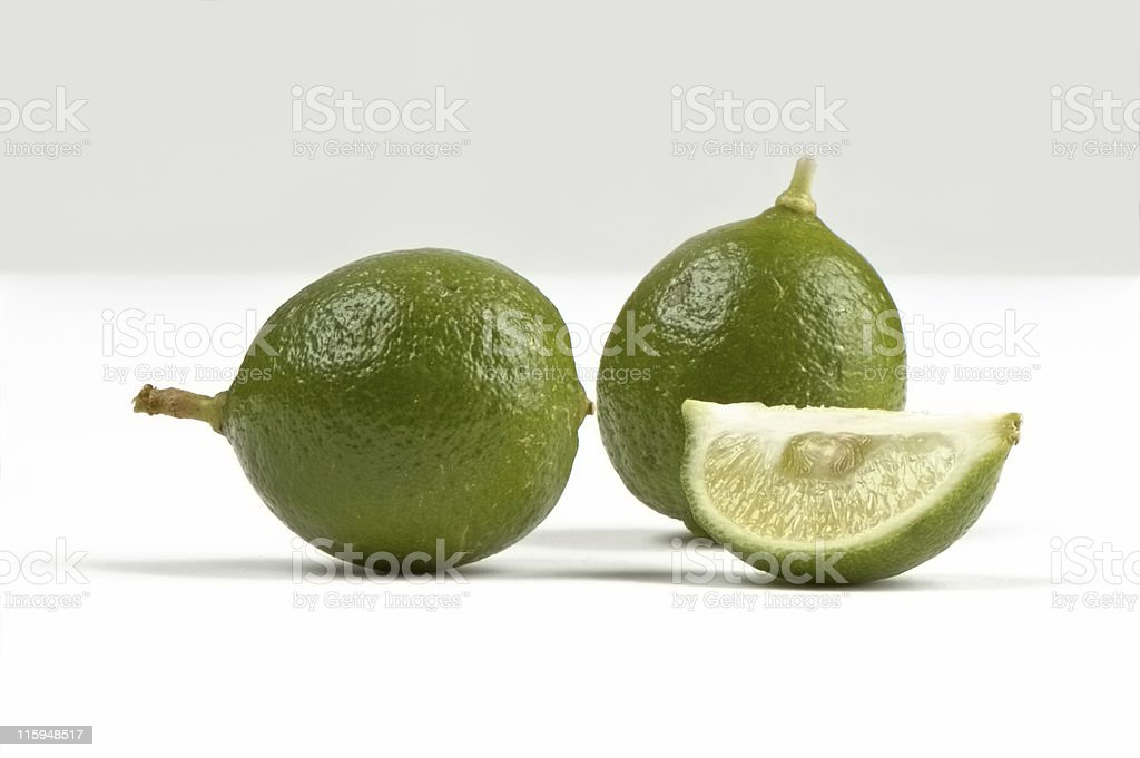 Key Limes on a white background one is sliced stock photo