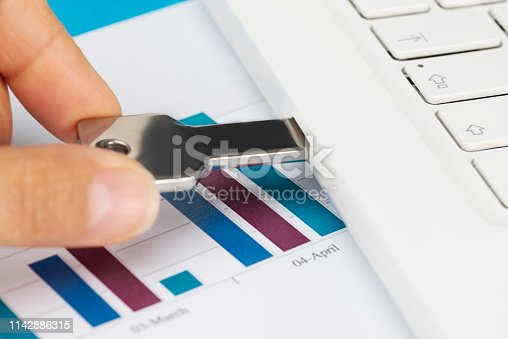 Hand is holding silver colored USB stick attached to laptop on table with chart including documents.
