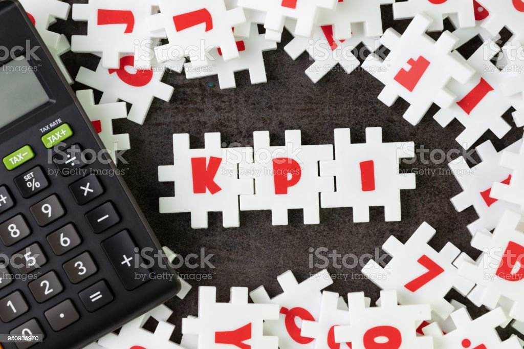 KPI, Key Point Indicator concept, white puzzle jigsaw alphabet combine word KPI at the center with calculator on dark black cement floor, business success target and measurement stock photo