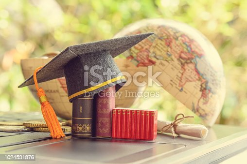 istock Key success in graduate study abroad program and open or expand world view experience concept : Graduation cap or hat, certificate or diploma, mini text books on a laptop computer, a half world globe. 1024531876