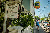 Key West, Florida, United States - August 15, 2018: Image of a placard, a building and people on the streets downtown in Key West, Florida Keys - United States