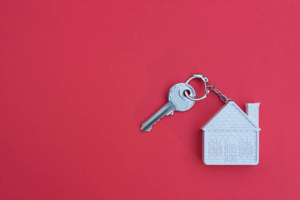 Key with a keychain in the form of a house on a red background. The concept of buying, selling, renting real estate, mortgages, your own home. Place for text stock photo