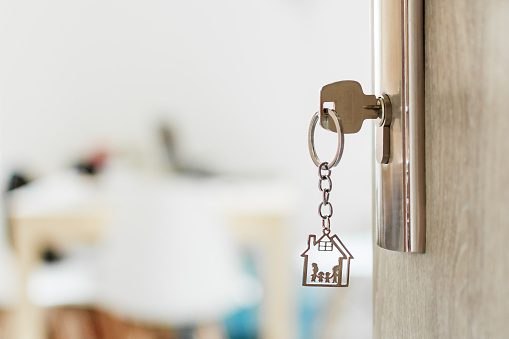 Key with keychain in a house shape and family in the door keyhole. Buy new home concept. Real estate market.