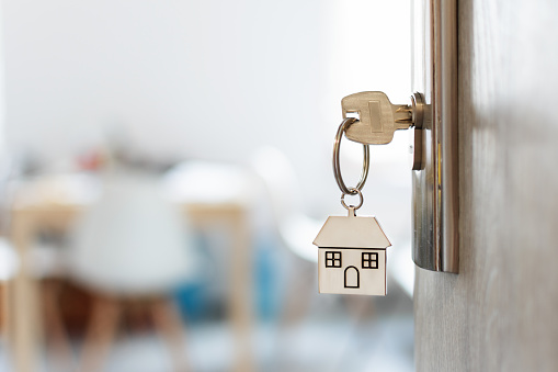 Key with keychain in a house shape in the door keyhole. Buy new home concept. Real estate market.