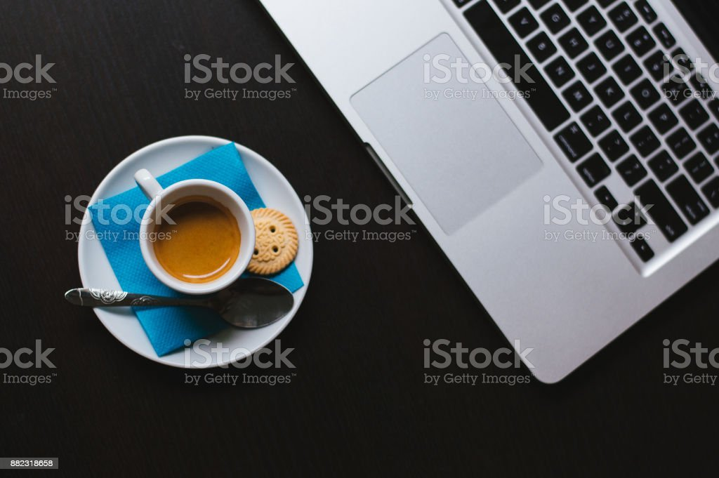 Keyboard and cup of coffee on a wooden background stock photo