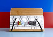 Keyboard and fake news text on multi colored wooden background