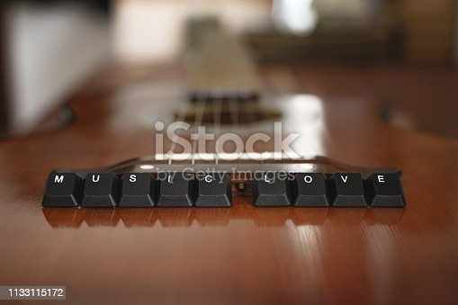 istock Keyboard buttons lettering music love on top of the Acoustic guitar. Red wooden background 1133115172