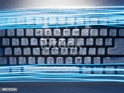 1128981457 istock photo keyboard covered with snow illuminated by blue light with lines painted by blue light with happy new year 2018 title 880753294