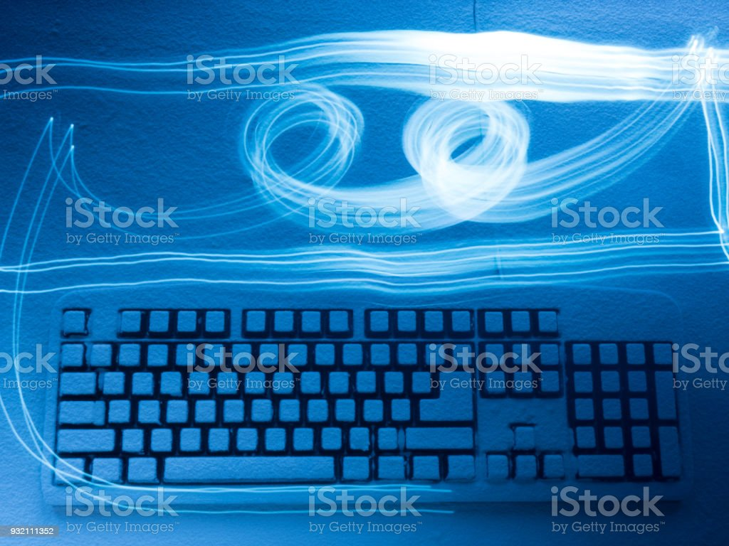 PC keyboard covered with snow illuminated by blue light with traces from drawing by freezelight stock photo