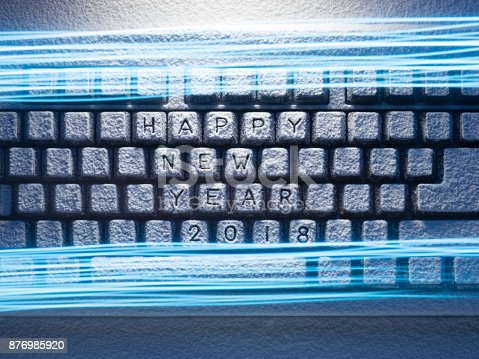 istock keyboard covered with snow with inscription happy new year 2018 with painted with light lines 876985920