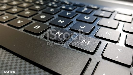 keyboard in side angle focused on the letter M. Keyboard in shades of gray and black