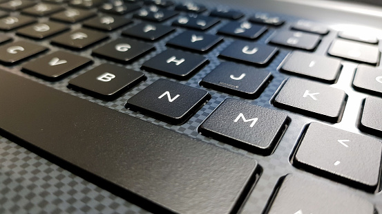 keyboard in side angle focused on the letter M. Keyboard in shades of gray and black.