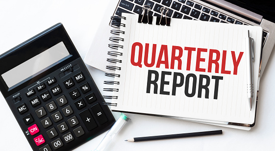 Keyboard of laptop, calcualtor, pencil and notepad with text QUARTERLY REPORT on the white background