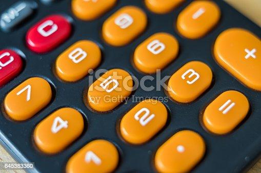 Keyboard of old pocket calculator. Orange and red keys on black background.